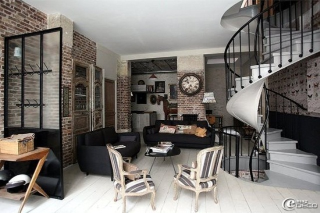 a gorgeous living room with brick walls, dark upholstered furniture, wooden coffee tables and a vintage clock