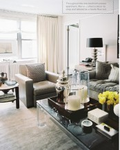 a neutral masculine living room with leather upholstered furniture, an acrylic table, neutral textiles and a black lamp