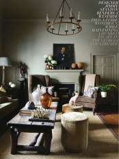 a moody living room with grey walls, a fireplace, cozy upholstered furniture, a rough wooden table and a chandelier