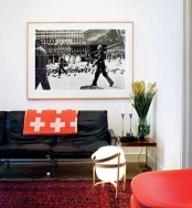 a bright living room done in white, black and red, with prints and an artwork for a bold look
