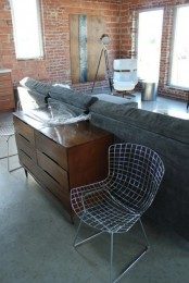 an industrial living room with brick walls, upholstered furniture, a wooden sideboard, metal lamps and a coffee table plus a wire chair