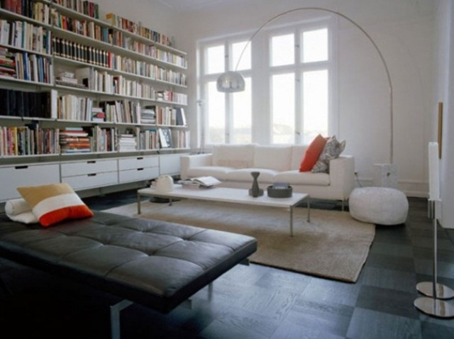 a contemporary living room with neutral and black upholstered furniture, floor lamps and a large bookshelf