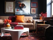 a moody living room with dark walls, a printed rug, neutral leather furniture, artworks and a white table