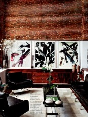 a sophisticated masculine living room with brick walls, artworks, black leather furniture and some blooms