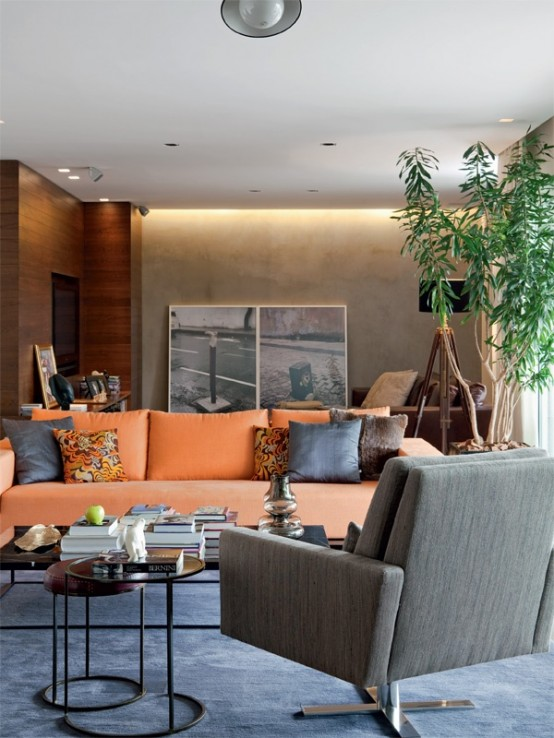 a bright modern living room with orange furniture, printed pillows, a potted plant, artworks, a floor lamp and coffee tables