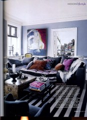 a moody living room with blue walls, dark furniture, printed pillows and an artwork plus a wooden chest coffee table