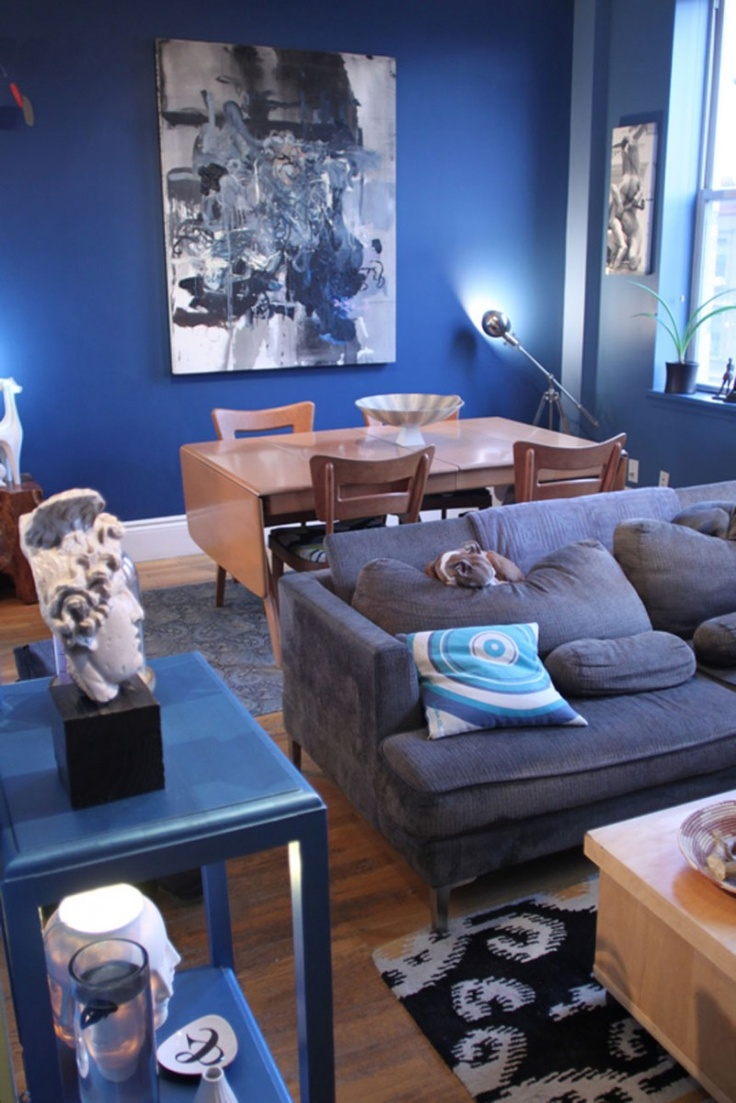 a bright masculine living room with blue walls, comfy upholstered furniture, bright accents and an artwork