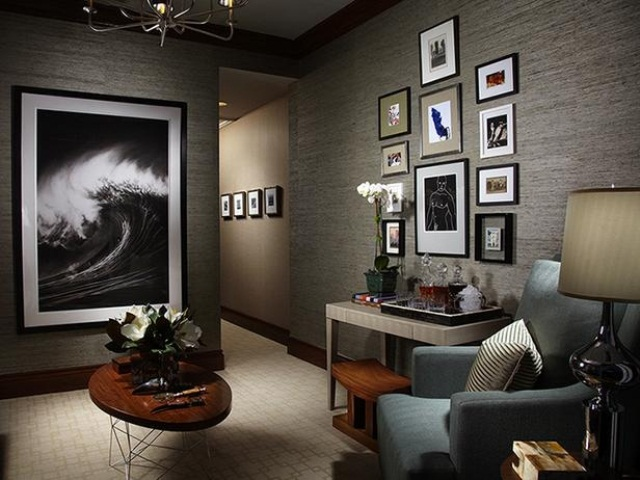 a moody masculine living room with a gallery wall, comfy aqua furniture, coffe tables and a large artrwork