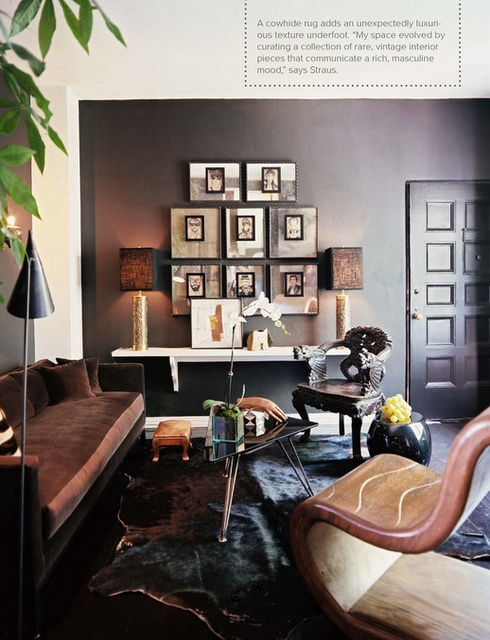 a dark masculine living room with dark walls, refined upholstered furniture, chic lamps, artworks and a catchy glass coffee table