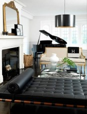 a sophisticated living room done in black and white, with refined furniture and a piano, lamps and a mirror plus a fireplace