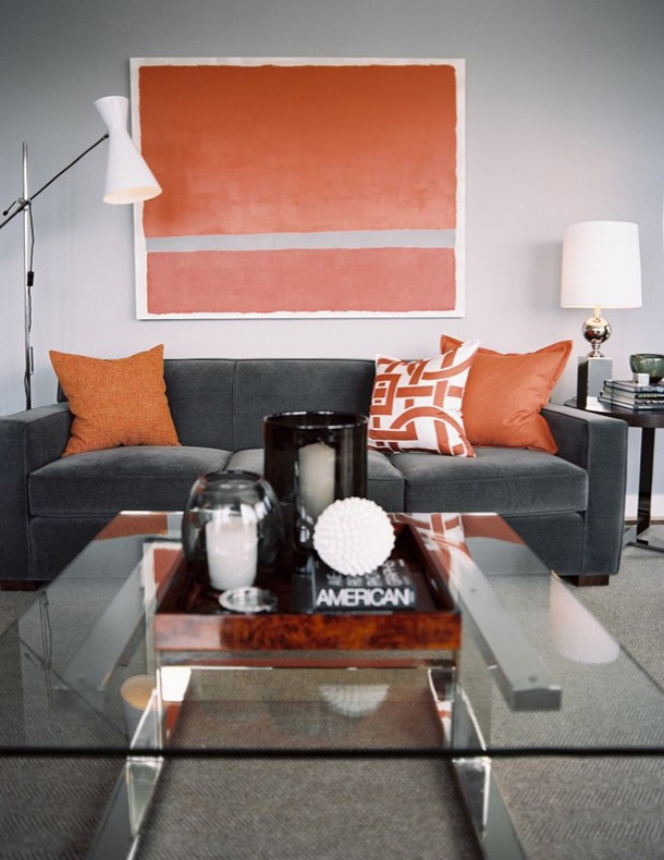 a bright modern living room with a grey sofa, a colorful artwork and matching pillows plus a glass coffee table and neutral lamps