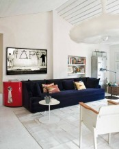 a neutral living room with a navy sofa and a red side table for a touch of color, artworks and storage units plus lamps