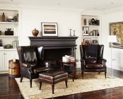 a sophisticated living room with all neutrals, dark leather furniture, a dark fireplace plus built-in storage units