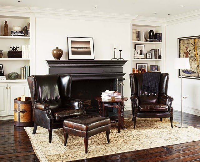 a sophisticated living room with all neutrals, dark leather furniture, a dark fireplace plus built in storage units