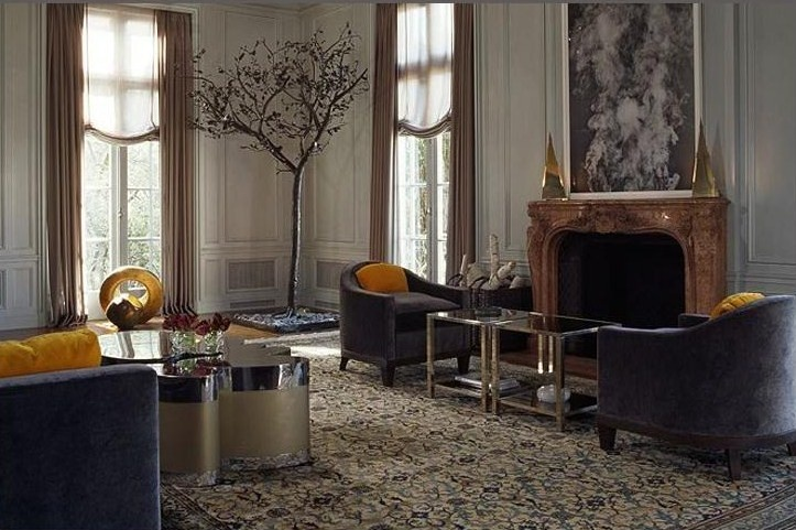 a refined living room with elegant furniture, gilded touches, a fireplace, a large artwork and curtains