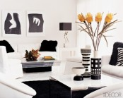 a minimalist black and white living room with rugs and fur pillows, abstract artworks and bright blooms