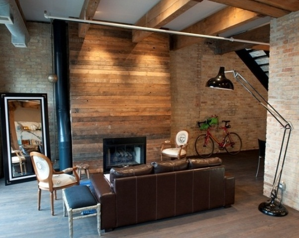 a laconic industrial living space with a wood clad fireplace wall, a floor lamp, refined chairs and a leather sofa
