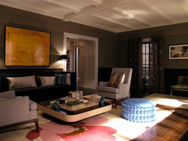 a dark living room with grey walls, neutral and dark upholstered furniture, an artwork, a rug and a blue ottoman