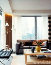 a comfy contemporary living room with much natural light, dark furniture, a stone coffee table and lamps