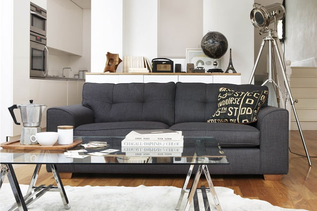 a contemporayr living room with a grey sofa, a glass coffee table, a floor lamp, some storage units and a rug