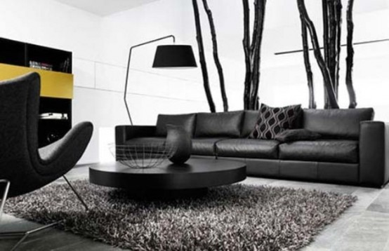 a minimalist masculine living room with dark furniture, a round coffee table, a floor lamp and a bright storage unit