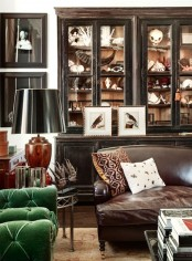 a chic and elegant living room done with dark furniture, a green velvet chair for a touch of color, artworks, lamps and skulls in glass armoires