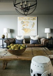 a stylish masculine space with grey walls, a leather sofa, a wooden coffee table, a metal sphere chandelier and artworks