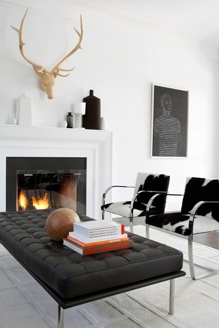 an elegant minimalist living room with a fireplace, a black leather couch, animl print chairs and artworks