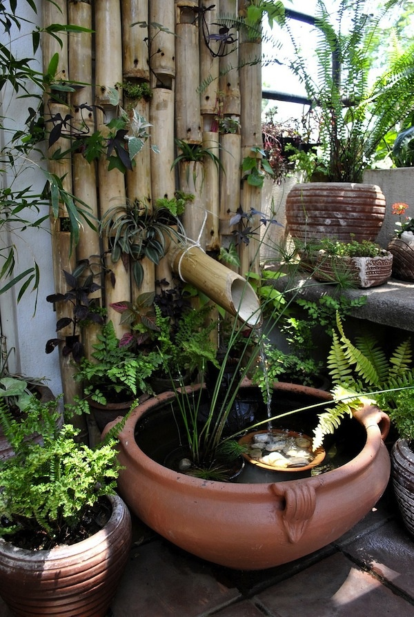 a Japanese inspired bamboo wall with greenery, a porcelain bowl and pebbles and greenery plus a bamboo fountain