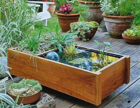 a wooden box mini pond with water plants, a clear ball and a usual planter in the second part