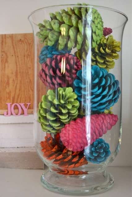 Spray painted pinecones really pop placed in a tall vase.