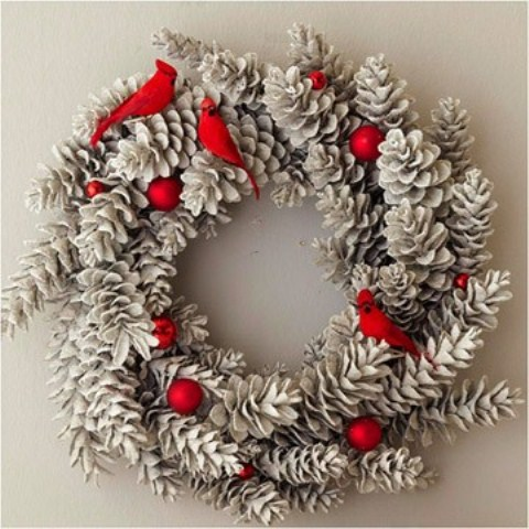 A faux frost-tipped wreath, made using pinecones and red ornaments could add a