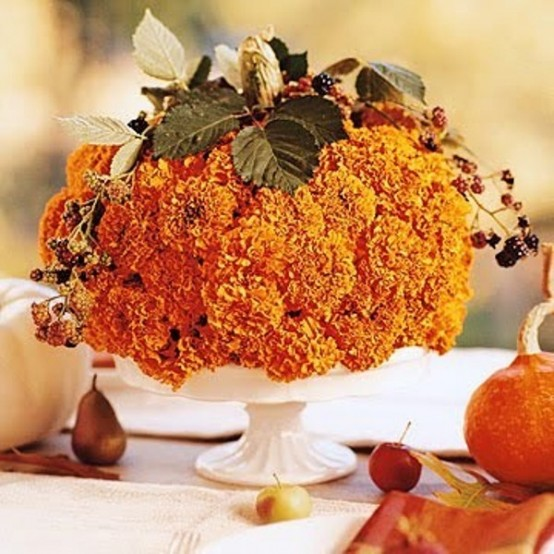 Cover the whole pumpkin with autumn blooms and put in on a cake stand. You'd only need to drill a bunch of holes in it.