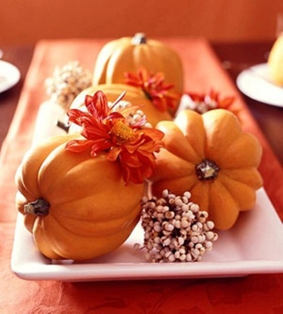 Several small pumpkins mixed with fall blooms or fallen leaves could fit a single plate. Such centerpiece is easy to move around when necessary.