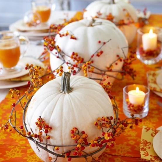 White pumpkins encircled by bittersweet vine and surrounded by candles make a perfect arrangement on an orange table runner.