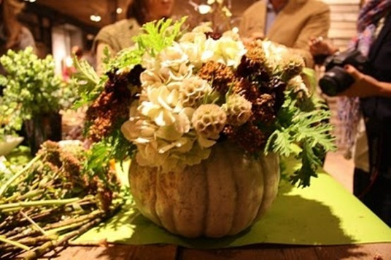 Hollow out the pumpkin, then place a of fall blooms and berries inside. That's all you need to do to make a natural piece of table decor.