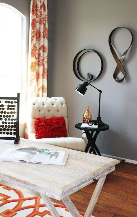 a modern farmhouse home office with grey walls, a white desk and chair, colorful textiles and a cozy reading nook with a side table