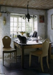 a rustic vintage home office with white plaster walls, wooden furniture and chairs, a vintage lamp and some artworks