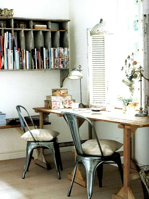 a rustic industrial home office in neutrals, with a wooden trestle desk, a large shelving unit on the wall and potted plants and blooms