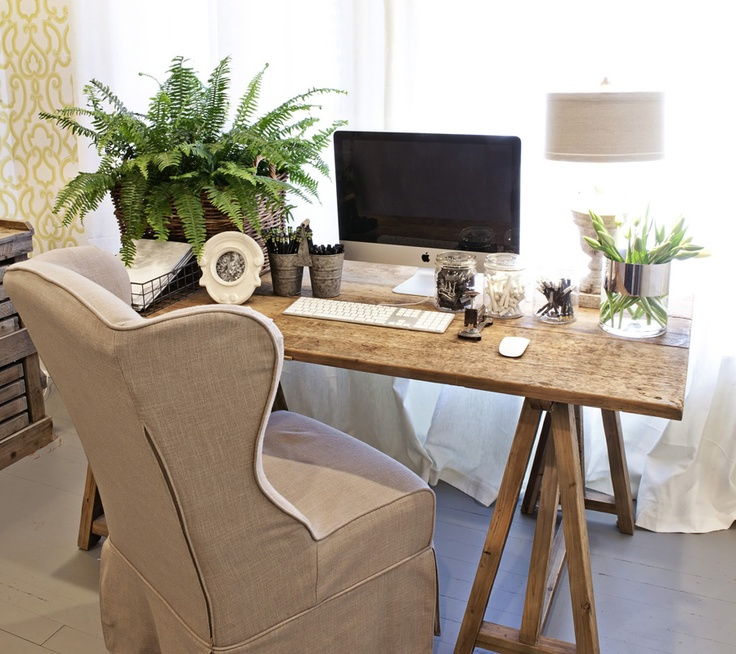 a small rustic home office with a trestle desk, a burlap chair, potted greenery and lamps is a cozy space