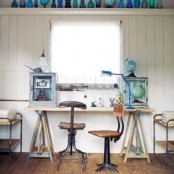 a rustic coastal home office wiht white walls, a trestle desk, industrial chairs and some blue bottles and vases for decorating