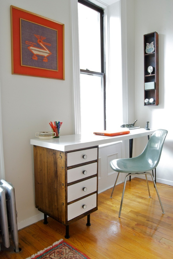 a modern rustic home office with a mid century modern desk, a blue chair, a bright artwork and a shelving unit on the wall
