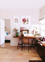 a vintage rustic home office with a trestle desk, dark tables and a bright gallery wall with flower art works