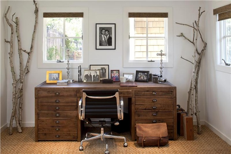 a neutral rustic home office with a wooden desk, tree branches, a jute rug, burlap shutters and a stylish mid century modern chair