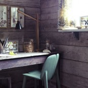 a rustic home office with wooden walls, a wooden desk, a green chair, a wooden lamp and some artworks on the wall