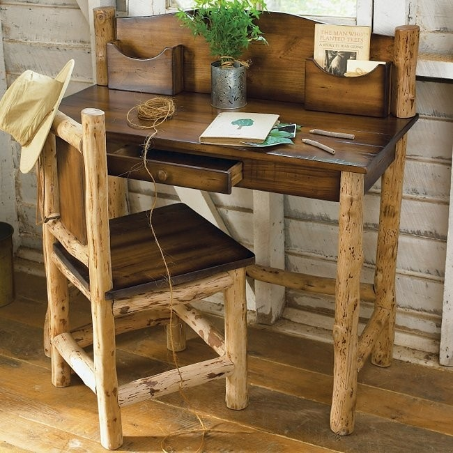 a rustic home office with whitewashed wooden walls, a dark stained desk and chair plus greenery in a pot