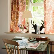 a bright rustic home office with colorful curtains, a shabby chic desk, wooden chairs, a table lamp and some decor