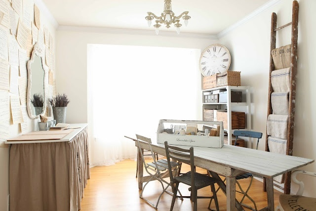 a neutral rustic home office with a large shelving unit, a table with curtains and a rustic desk and chairs