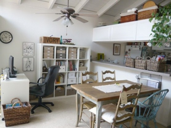 a neutral contemporary home office with sleek white furniture, rustic desks, potted greenery and blooms