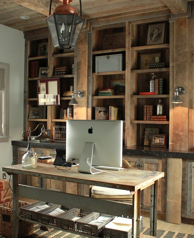 a rustic industrial home office with a large open storage unit, an industrial desk, a pendant vintage lamp and matching sconces on the shelving unit